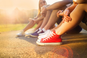 Legs and sneakers of teenage boys and girls sitting on the sidewalk