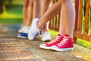 Legs and sneakers of teenage boys and girls standing on the sidewalk