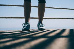 Legs of a young athletic woman in blue sneakers against the background of the sea in the morning light close-up. Concept of a healthy lifestyle.