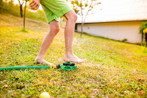 Legs of a young boy in a summer garden at the sprinkler