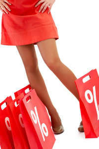 Legs of lady standing by red paper bags