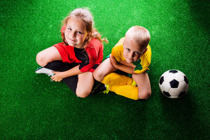 Legs of two unrecognizable little football players with soccer ball against artificial grass. Studio shot on green background.