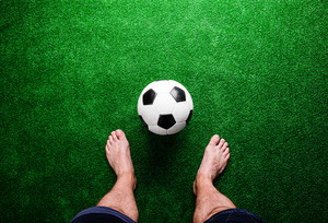 Legs of unrecognizable barefoot football player against artificial grass. Studio shot on green grass.