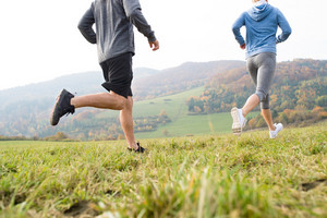 Legs of unrecognizable couple running in colorful autumn nature. Close up. Rear view.