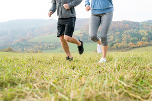 Legs of unrecognizable couple running in colorful autumn nature. Close up.