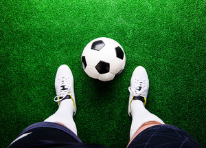 Legs of unrecognizable football player against artificial grass. Studio shot on green grass.