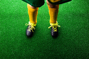 Legs of unrecognizable little football player in cleats against artificial grass. Studio shot on green grass. Copy space.
