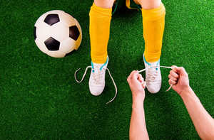 Legs of unrecognizable little football player in yellow knee socks with soccer ball having his shoelaces tied by his father, against artificial grass. Studio shot on green background.