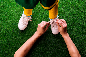 Legs of unrecognizable little football player in yellow knee socks with soccer, having his shoelaces tied by his father, against artificial grass. Studio shot on green background.