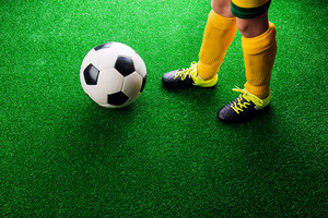 Legs of unrecognizable little football player with soccer ball against artificial grass. Studio shot on green grass. Copy space.