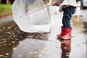 Legs of unrecognizable little girl with the transparent umbrella in town on a rainy day.