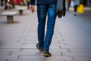 Legs of unrecognizable manager walking in the street of London, back view