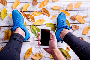 Legs of unrecognizable runner in blue sports shoes. Smart phone and earphones. Colorful autumn leaves. Studio shot on white wooden background.