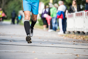 Legs of unrecognizable runner sprinting outdoors. Sportive people competing in a urban area, healthy lifestyle and sport concepts.