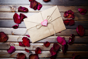 Letter of congratulations sealed by small decorative heart on its top and rose petals around