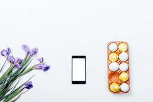 Lilac irises, mobile phone and tray with painted Easter eggs on white background, top view