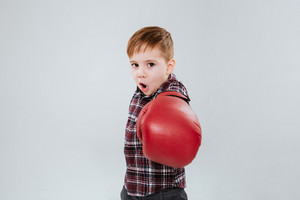 Litle boy in boxing gloves standing and fighting over white background