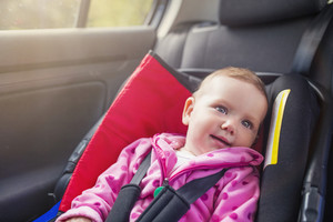 Little baby girl in a car in a child seat