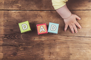 Little baby with cubes with dad sign on wooden background