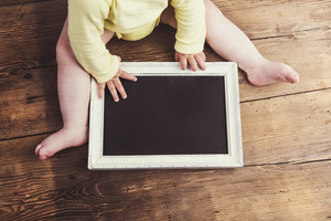 Little baby with empty picture frame on wooden background