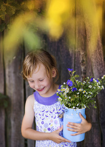 Little blonde girl holding meadow flowers laughing by the wooden fence