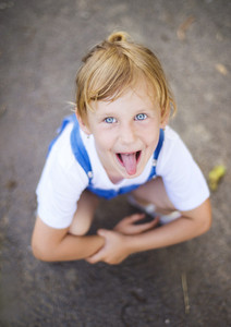 Little blonde girl with blue eyes sticks out tongue.