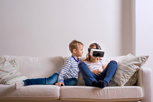 Little boy and girl wearing virtual reality goggles. Studio shot, white couch