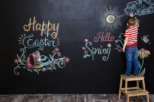 Little boy drawing easter doodles on chalk black board while standing on the ladder