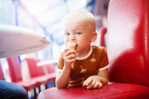Little boy enjoying ice cream in cafe