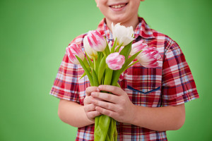 Little boy holding bunch of white and pink tulips