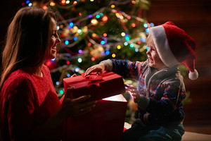 Little boy in Santa cap opening big giftbox while looking at his mother