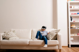 Little boy in striped t-shirt wearing virtual reality goggles, sitting on white couch in a living room