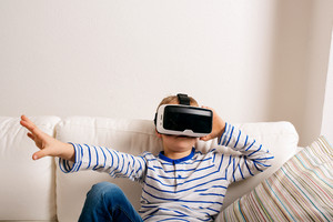Little boy in striped t-shirt wearing virtual reality goggles. Sitting on white couch, reaching out, studio shot