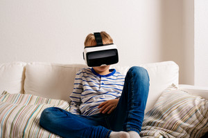 Little boy in striped t-shirt wearing virtual reality goggles. Sitting on white couch, studio shot
