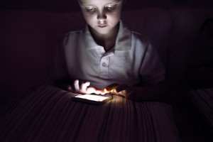 Little boy playing with smart phone, sitting on sofa in dark room at night.