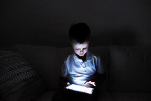 Little boy playing with tablet, sitting on sofa in dark room at night.