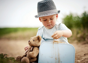 Little boy playing with teddy bear on the footpath