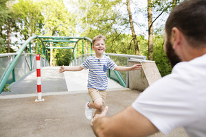 Little boy running into the arms of his father, sunny summer day.
