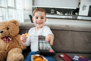 Little boy sitting on sofa with teddy bear at home and watching TV while eating chips. Holding remote control.