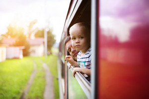 Little boy traveling in train looking outside the window.