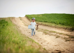 Little boy walking on the footpath in field with suitacase and teddy bear