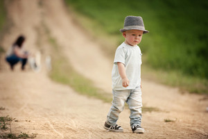 Little boy walking on the footpath in field