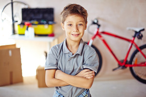 Little boy with crossed arms looking at camera in garage