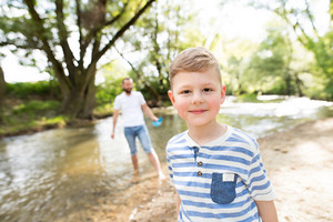 Little boy with his father at the river having fun, sunny spring day.