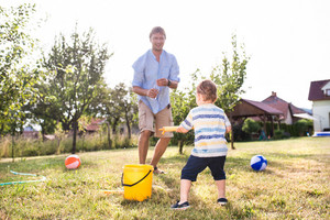 Little boy with his father playing with water guns, splashing, fun in garden, sunny summer day, back yard