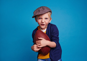 Little boy with rugby ball over blue background