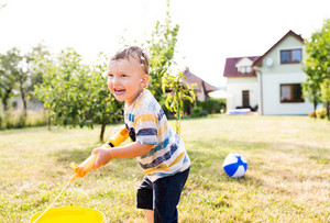 Little boy with water gun splashing somebody, fun in garden, sunny summer day, back yard