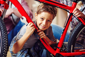 Little boy with wrench looking at camera in garage