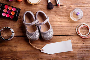 Little childrens silver shoes tag and various make up products. Studio shot on wooden background. Copy space.