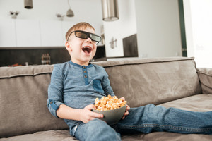 Little cute boy sitting on sofa watching TV with 3d glasses holding popcorn in hands.
